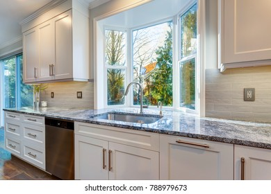 Luxury home interior boasts amazing kitchen with custom white shaker cabinets topped with granite fitted with a wide stainless steel sink and pull out faucet placed under the window.