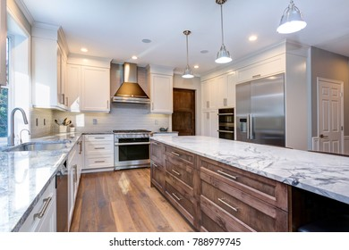 Luxury home interior boasts amazing kitchen with custom white shaker cabinets, endless marble topped island with drawers and stainless steel appliances over wide planked hardwood floor.