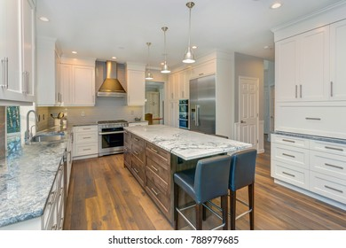 Luxury home interior boasts Beautiful kitchen with custom white shaker cabinets, endless marble topped island with black leather stools over wide planked hardwood floor.