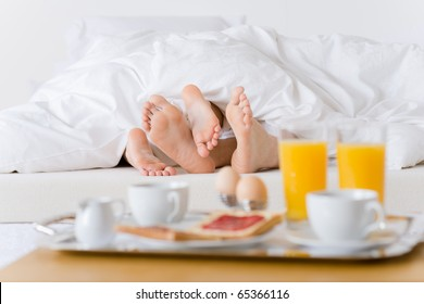 Luxury hotel honeymoon breakfast - couple in white bed together