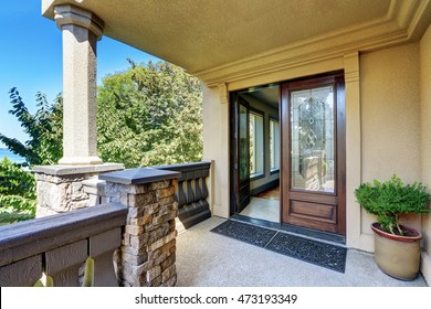 Luxury house exterior. Entrance column porch with railings and rug Open front door. Northwest, USA
