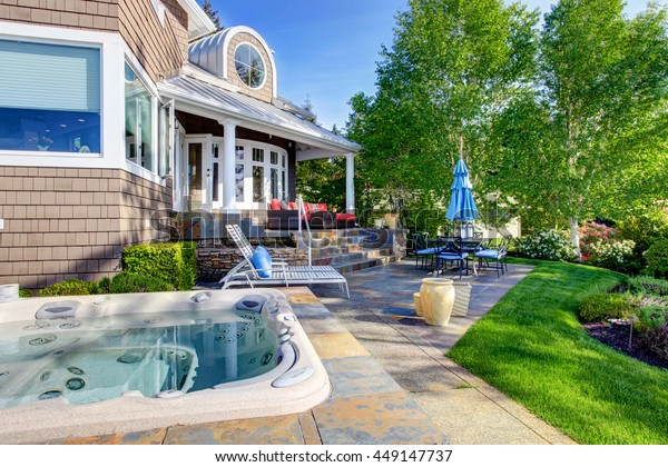 Luxury house exterior with impressive backyard design, patio and sitting area and hot tub.