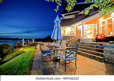 Luxury house exterior with impressive water view and cozy patio area. Summer evening.
