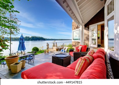 Luxury house exterior with impressive water view, cozy patio area and sitting place with wicker sofa and red pillows.