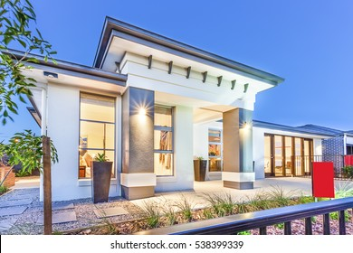 Luxury house facade over the metal fence under blue sky, there are trees and gravel on the ground of small garden, flower vases can see on the floor, green grass around the area.