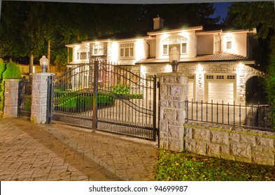 A luxury house with the gates in suburbs at dusk in Vancouver, Canada