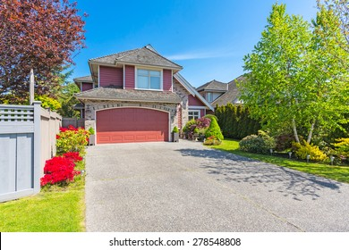 Luxury house with nicely trimmed and designed front yard, lawn in a residential neighbourhood in Canada.