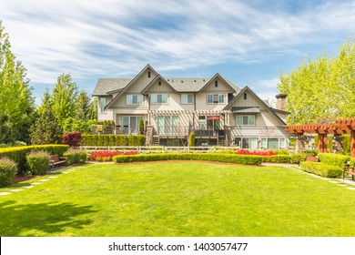 Luxury house in the suburbs of Canada with nicely trimmed and manicured garden, landscaping, on a sunny day.