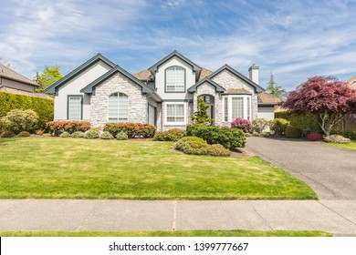 Luxury house in the suburbs of Canada in a quiet neighbourhood. Perfectly manicured front yard, beautifully done lanscaping with blooming flowers on a sunny summer day with a blue sky.