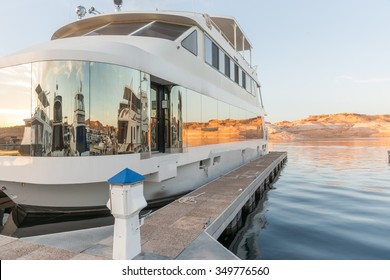 Luxury houseboat at pier on Lake Powell with window reflections of boats and red rock cliffs across lake Arizona USA