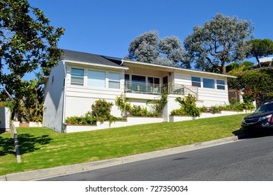 Luxury houses and estates with nicely landscaped front yard in an upscale neighborhood of Pacific Palisades, CA.
