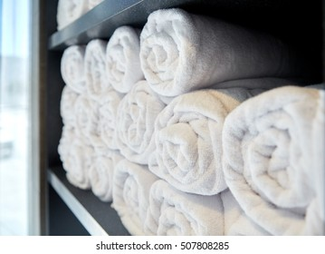 luxury and hygiene concept - rolled white bath towels at hotel spa