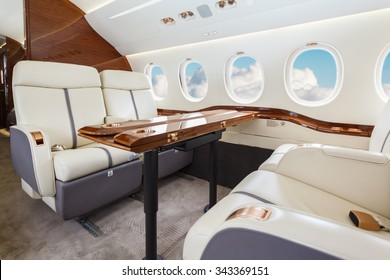 Luxury interior in bright colors of genuine leather in the business jet, sky and clouds through the porthole