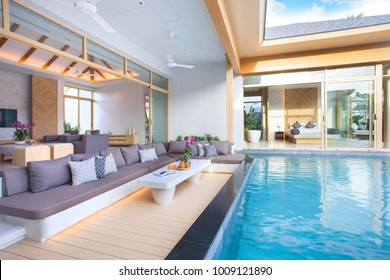 Luxury interior design in living room of pool villas. Airy and bright space with high raised ceiling and wooden dining table home, house ,sunbed ,building