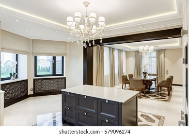 Luxury interior of dining room in beige, white and black colors. Kitchen bar of the center of room and crystal chandelier over. View of other room with big wooden table and chairs around.