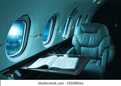 luxury interior in the modern  business jet and sunlight at the window/sky and clouds through the porthole/blue toned