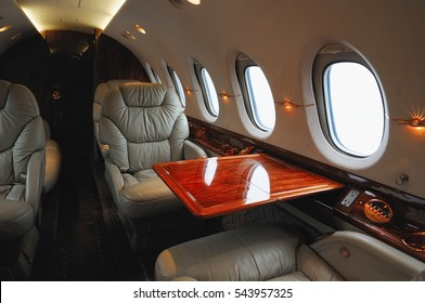 luxury interior in the modern  business jet and sunlight at the window/sky and clouds through the porthole