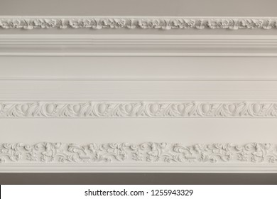 Luxury interior. Stucco elements on light wall. White patterned. Mouldings element from gypsum. Roccoco style