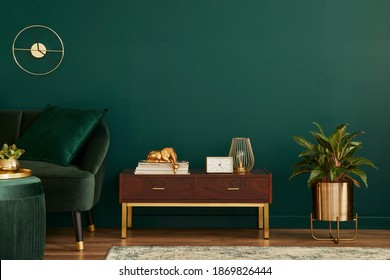 Luxury interior with stylish velvet sofa, wooden commode, pouf, plants, carpet, gold decoration, copy space and elegant personal accessories. Modern living room in classic house. Template. - Shutterstock ID 1869826444