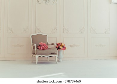 luxury interiors in beige tones. Elegant vintage armchair in a spacious room with a wall decorated with ornaments. colorful flowers in a vase standing on the wooden floor