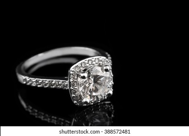 Luxury jewellery. White gold or silver engagement ring with diamonds closeup on black glass background. Selective focus.