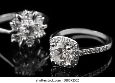 Luxury jewellery. White gold or silver engagement rings with diamonds closeup on black glass background. Selective focus.
