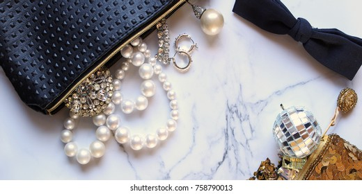 Luxury jewelry and bags spilling with items onto white marble copy space.