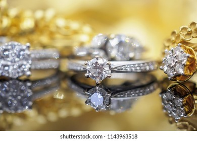 Luxury Jewelry diamond rings with reflection on black and golden background