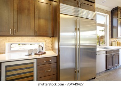 Luxury kitchen accented with large built-in stainless steel refrigerator framed by taupe tile backsplash and natural brown wood cabinets. Northwest, USA