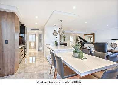 Luxury kitchen and dining area with the hallway reflection of a modern house or hotel, the tile floor go beside the stove and pantry near the counter and leather sofas with piano