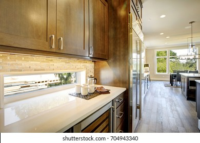 Luxury kitchen features brown wood front upper cabinets and shaker lower cabinets fitted with a glass door wine cooler paired with a white quartz countertop under a small window. Northwest, USA