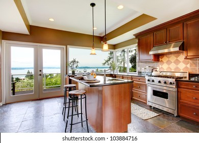 Luxury kitchen interior with green walls and stone floor and water view.