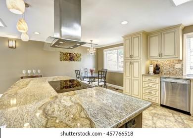 Luxury kitchen interior in light beige color with back splash trim and tile floor