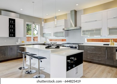 Luxury kitchen with  natural backsplash, white quartz, natural brown wood cabinets and lots of light. Northwest, USA