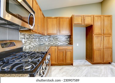 Luxury kitchen room with bright brown cabinets, mosaic backsplash trim and streel appliances.