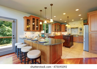 Luxury kitchen room interior with cabinets and granite counter tops. Bar counter with elegant pendant lights and dinner setting. Northwest, USA