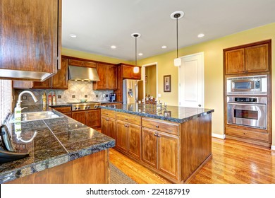 Luxury kitchen room with modern storage combination and steel stainless appliances. Big kitchen island with granite top