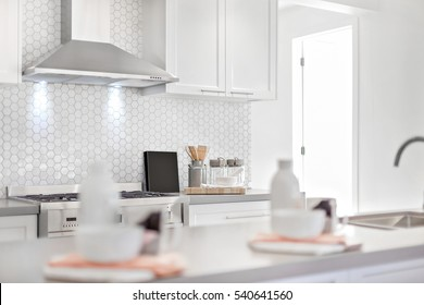 Luxury kitchen with silver chimney also door opened, there is a counter top and blurred, the stove and utensils beside bee net shape tiles, very clean area.