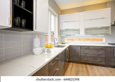 Luxury kitchen with white quartz, natural backsplash, natural brown wood cabinets, with lots of natural light. Northwest, USA