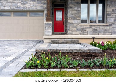Luxury landscaping of paver driveway, landing, and steps with matching pattern detail and front garden.