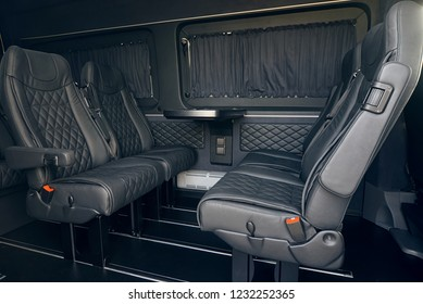 Luxury leather seats in the van. Interior of luxury minivan with open doors