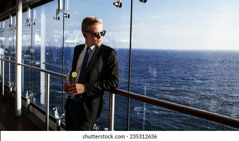 Luxury life. Portrait of the handsome and rich man. Shot from cruise liner. Sea on the background with copyspace