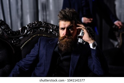 Luxury lifestyle, success, business, mafia, gangster concept. Criminal boss in luxury suit sits on vintage sofa. Mature man with beard. Bearded man with thoughtful, serious face in classic interior.