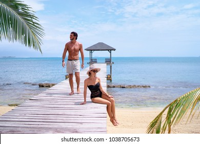 Luxury lifestyle and vacation. Tanning and sunbathing on the beach. Young womanand man in swimwear enjoying sea view on wooden pier.