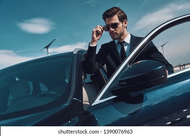 Luxury lifestyles. Handsome young man in business wear adjusting his sunglasses while standing near his car