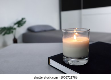 luxury lighting aromatic scent candle and a book is on the grey table to creat romantic and relax ambient in the grey bedroom with background of grey bed and pillow