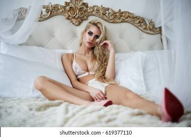 Luxury lingerie. Beautiful cute blond barbie girl with long hair and a slim body. In pink shoes and purple underwear.