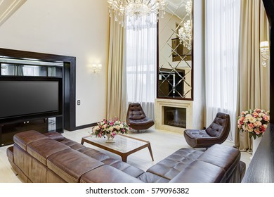 Luxury living room with brown leather armchair and sofa, place for TV set. Glasses table of center of room. Lighting room with brown, beige colors. Fireplace and mirror under.