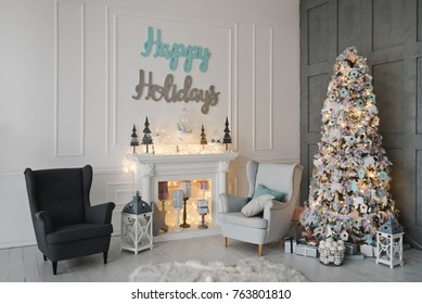 Luxury living room with a Christmas decor. Holiday background. New Year's decorations. New Year's decorations.  Fireplace with pink and blue candlesticks. The inscription on the wall - Happy Holidays