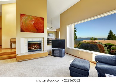 Luxury living room with high vaulted ceiling and large window with scenic bay view